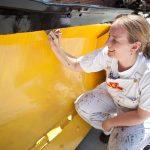 Volunteer painting TP-11 snow removal blade