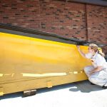 Volunteer painting TP-11 snow removal blade